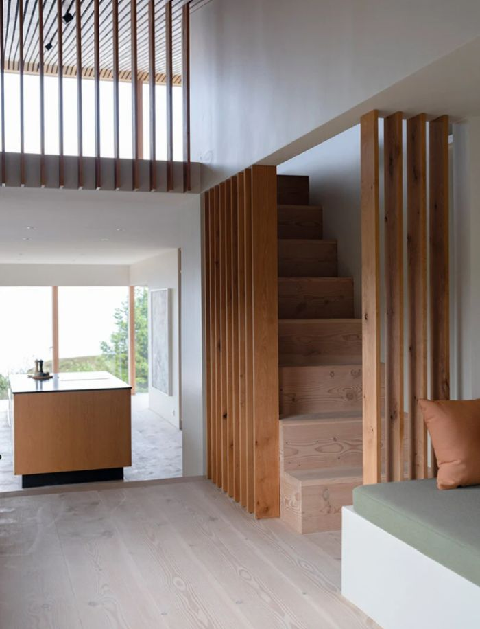 A wooden staircase leads up to the loft area from where the green roof of the house can be accessed