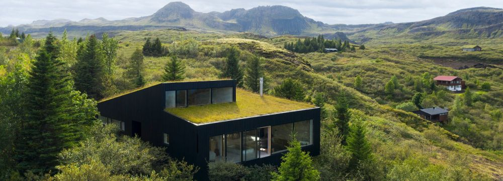 The green roof of the house is partially sloping towards the hillside