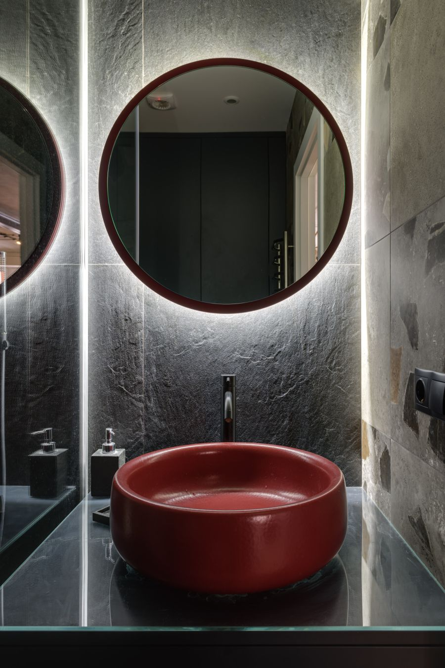 The red washbasin and circular mirror frame really help this bathroom pop in a chic way