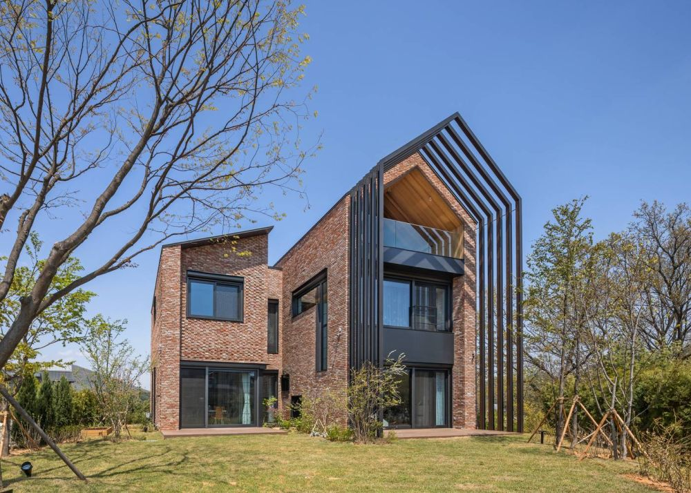 The exterior of the house features a modern design with a few graphic and sculptural details that emphasize the unique architecture