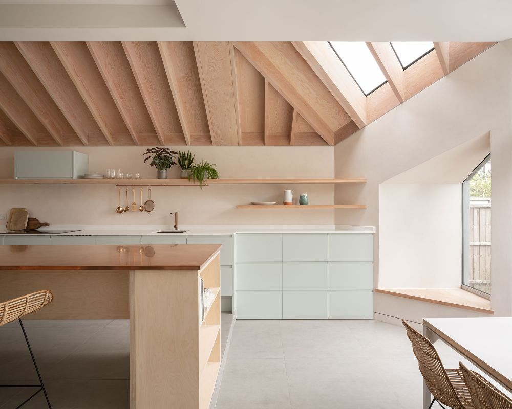 The kitchen has beautiful light green cabinetry and a stylish island with a copper top