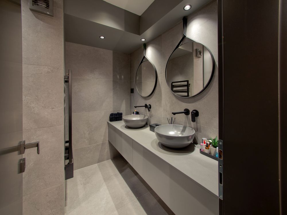 Subdued accent lighting and soft grey tones give the master bathroom a very inviting and pleasant look