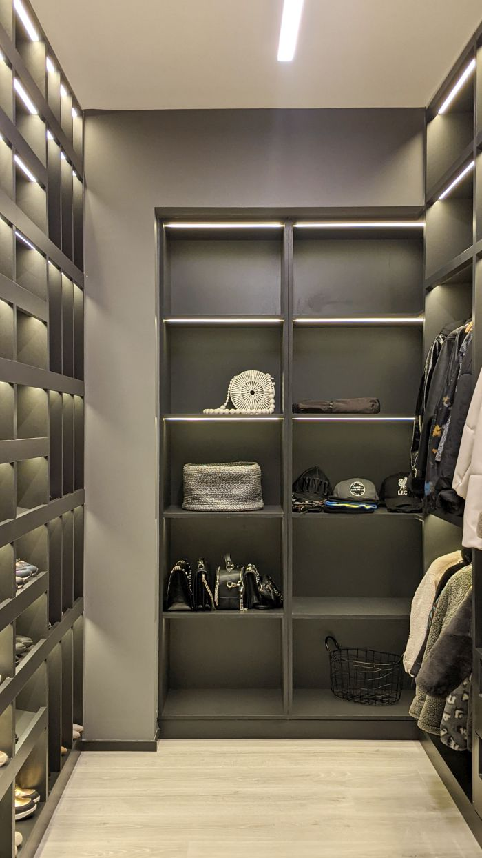 The walk-in closet matches the overall design of the bedroom and the apartment's color scheme