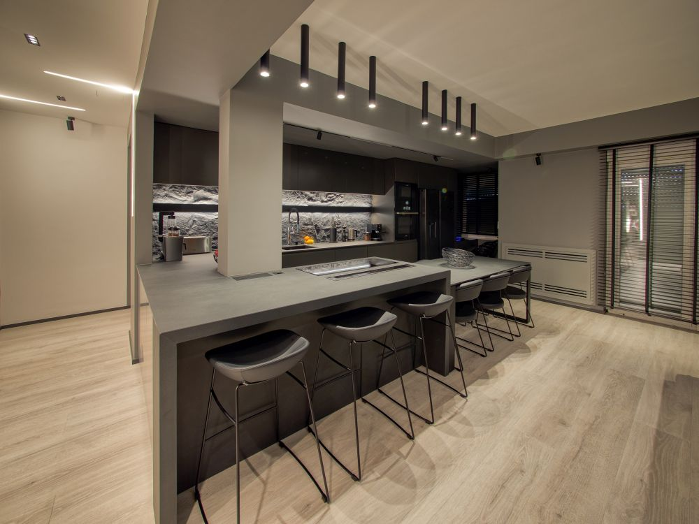 The kitchen island and the dining table have been combined into a large two-tier custom unit