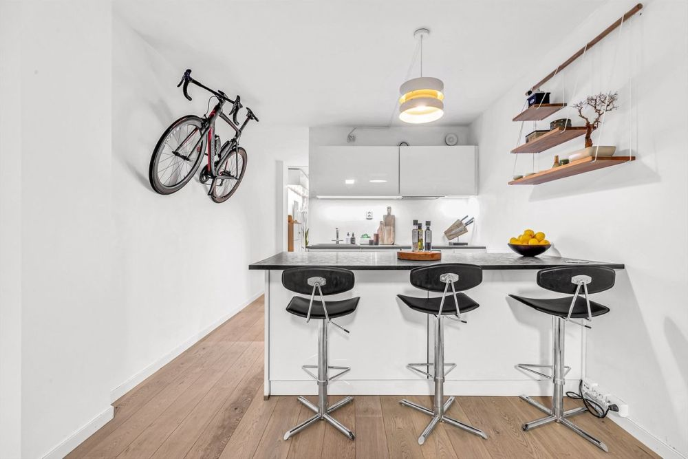 The kitchen is all white and makes the front section of the apartment look very bright, airy and inviting