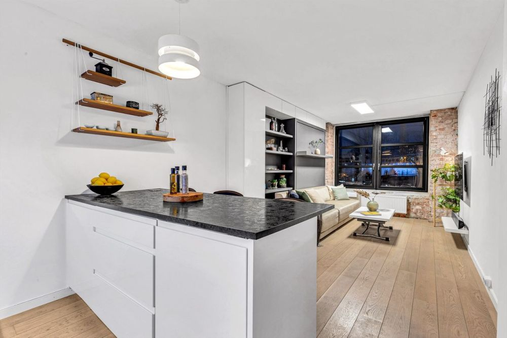 The small peninsula acts as a separator between the kitchen and the rest of the apartment