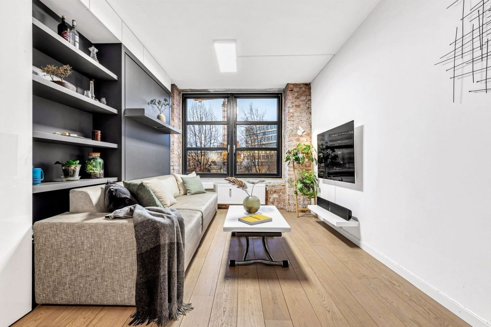 The exposed bricks add warmth, color and texture to this small apartment