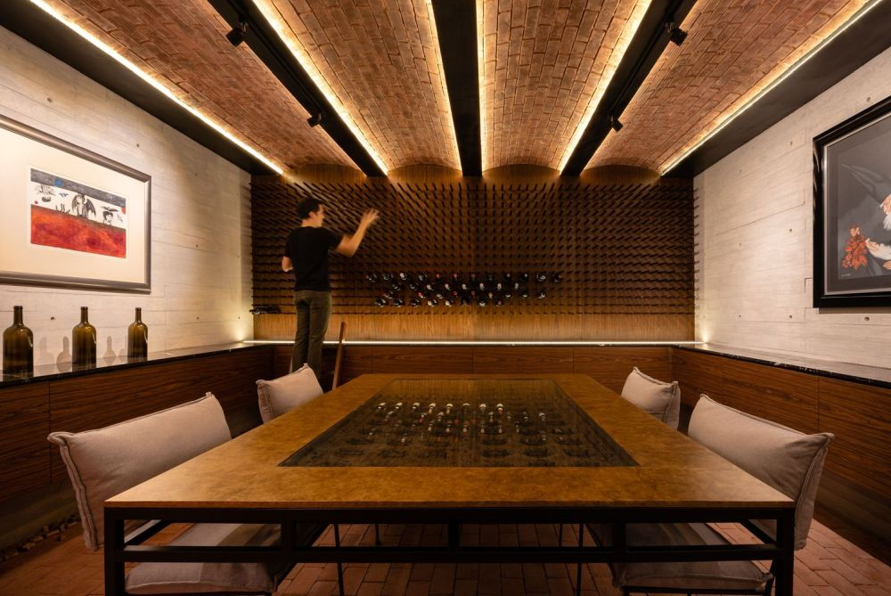 There's a wine cellar down in the basement with a big table in the middle and warm LED lights along the ceiling beams