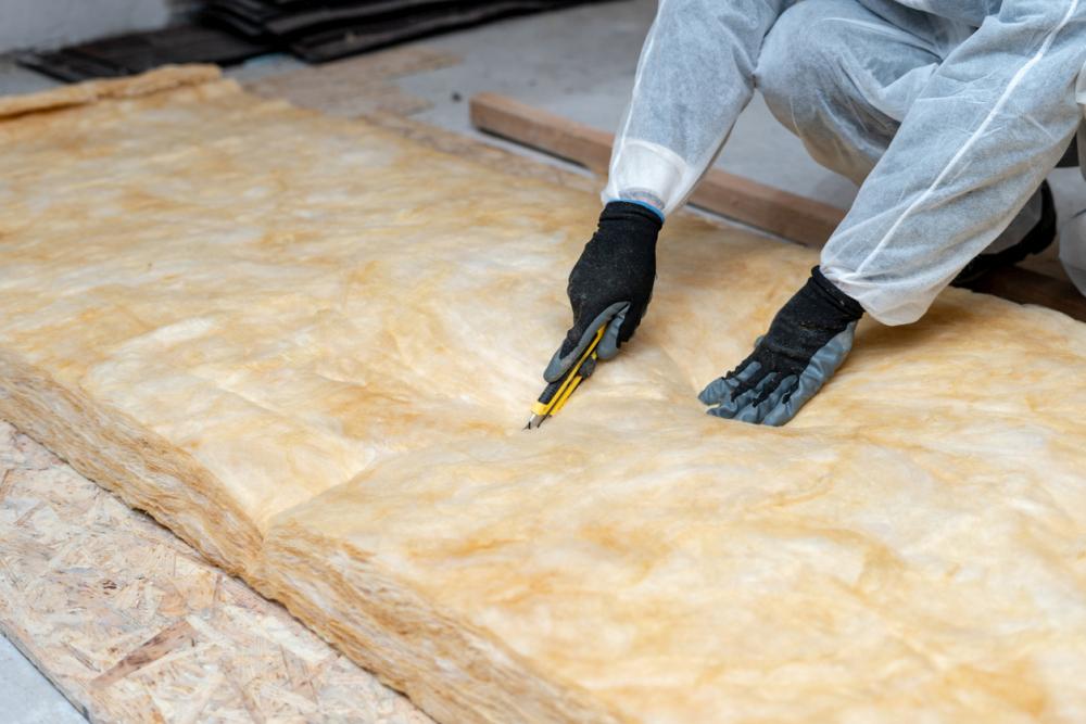 专业工人在屋顶下安装玻璃纤维棉保温层