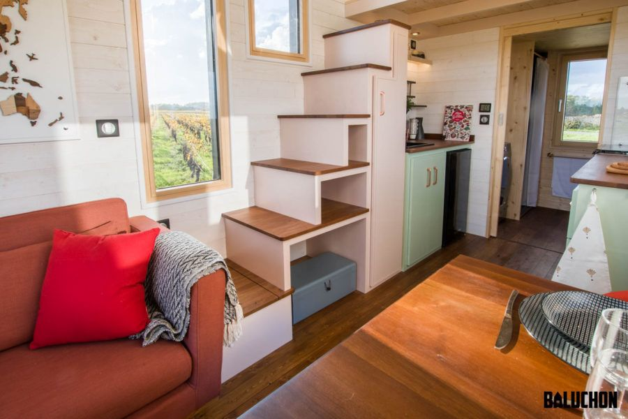 A set of stairs with built-in storage modules leads up to the loft bedroom
