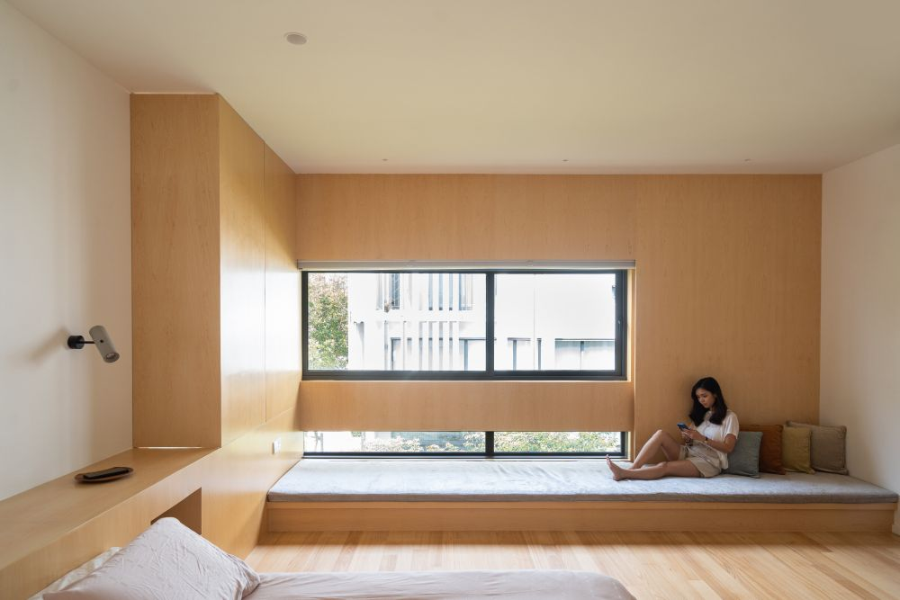 This bedroom has a long bench in front of the windows going from wall to wall
