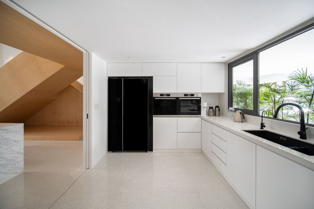 The kitchen is semi-open and was designed with a timeless black and white palette