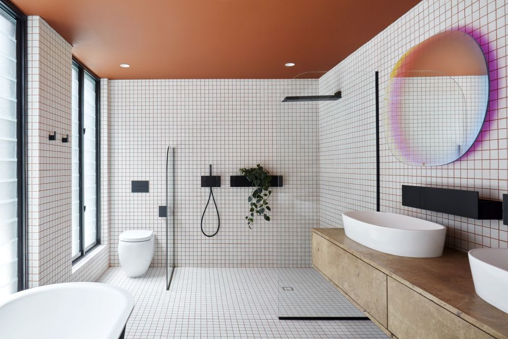 The colored ceiling and stylish wall mirror complement the monochrome look of this bathroom