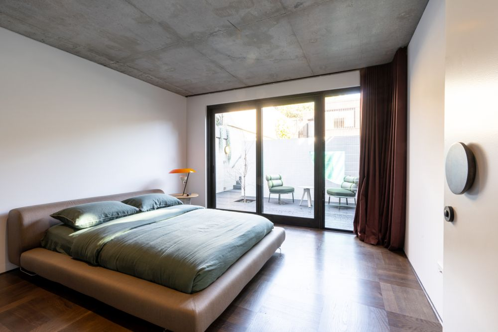 The raw concrete ceiling in the bedrooms is another detail borrowed from Japanese architecture