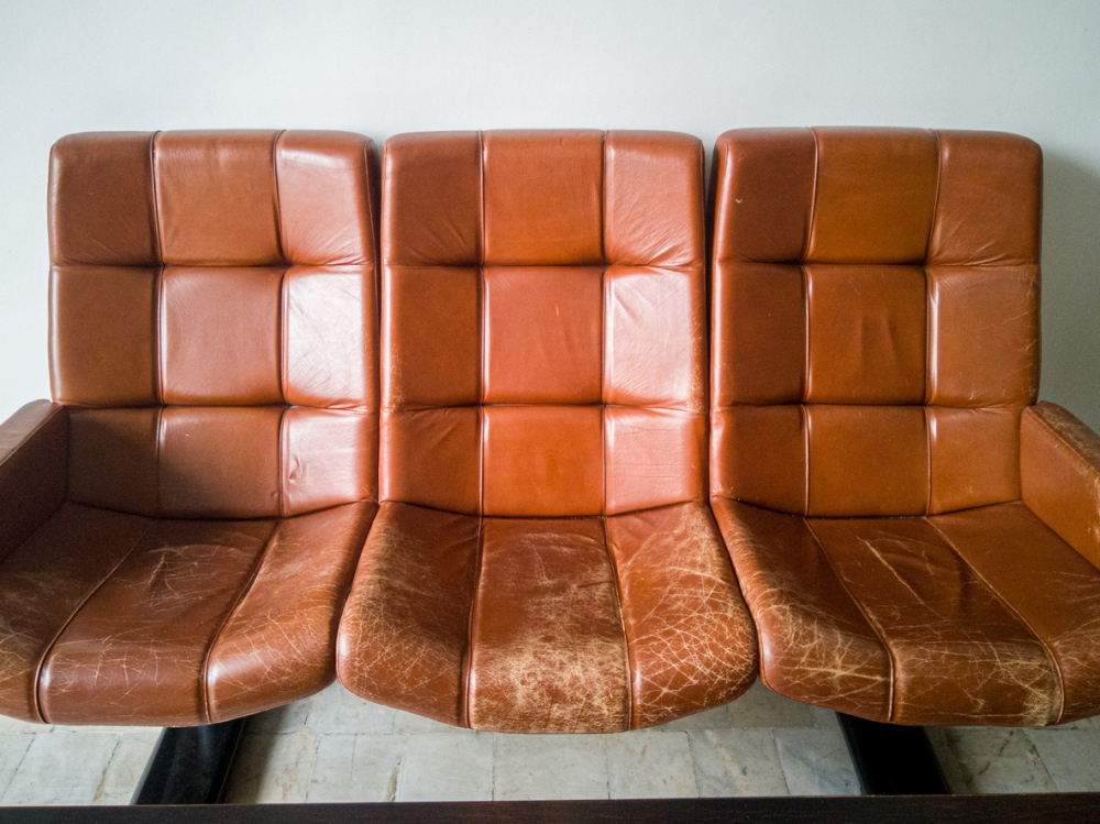 Old vintage brown leather armchairs. Cracked and worn skin from time and frequent use.