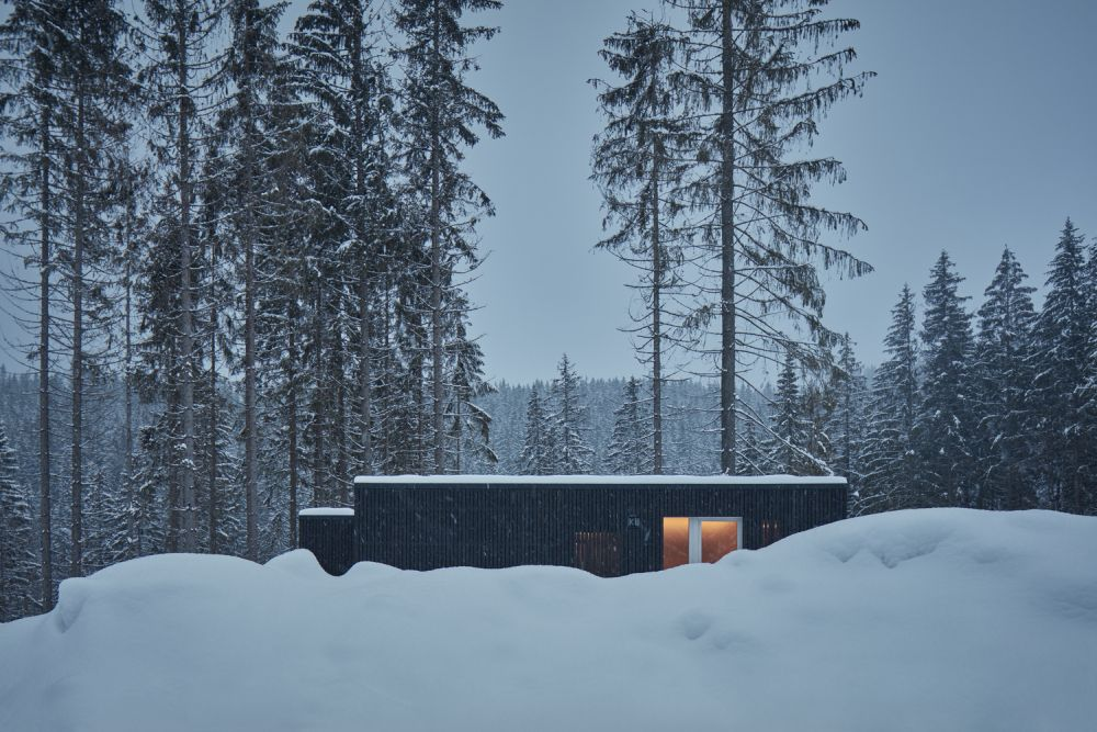 The dark exterior makes the cabins stand out against the snowy landscape and gives them a modern aesthetic