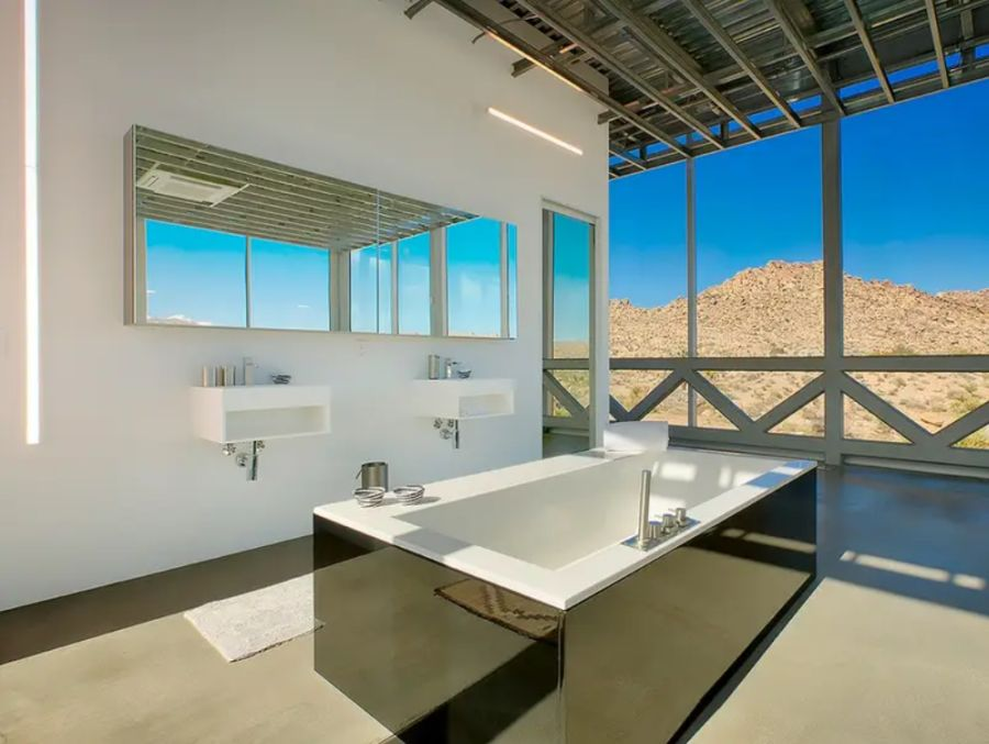 A freestanding tub with a mirrored frame emphasizes the cohesiveness between the interior and exterior design