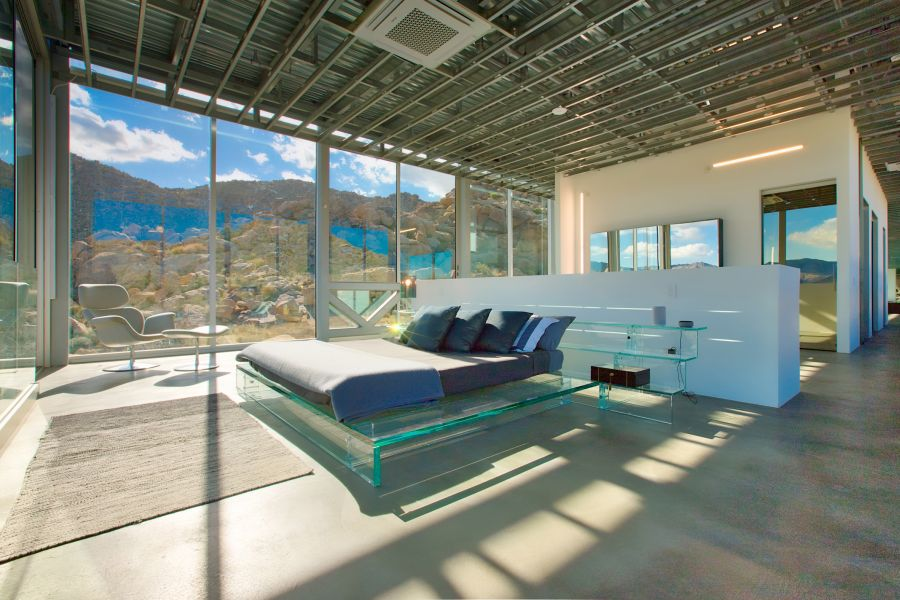 A glass bed frame gives this bedroom a very modern and airy aesthetic