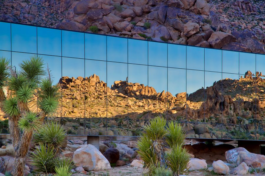 The mirrored facades of the house reflect the beautiful desert landscape
