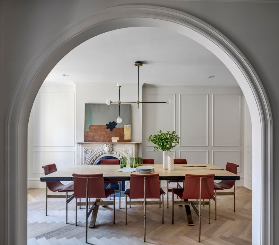 A beautiful arched doorway frames the dining room and the fireplace in the background