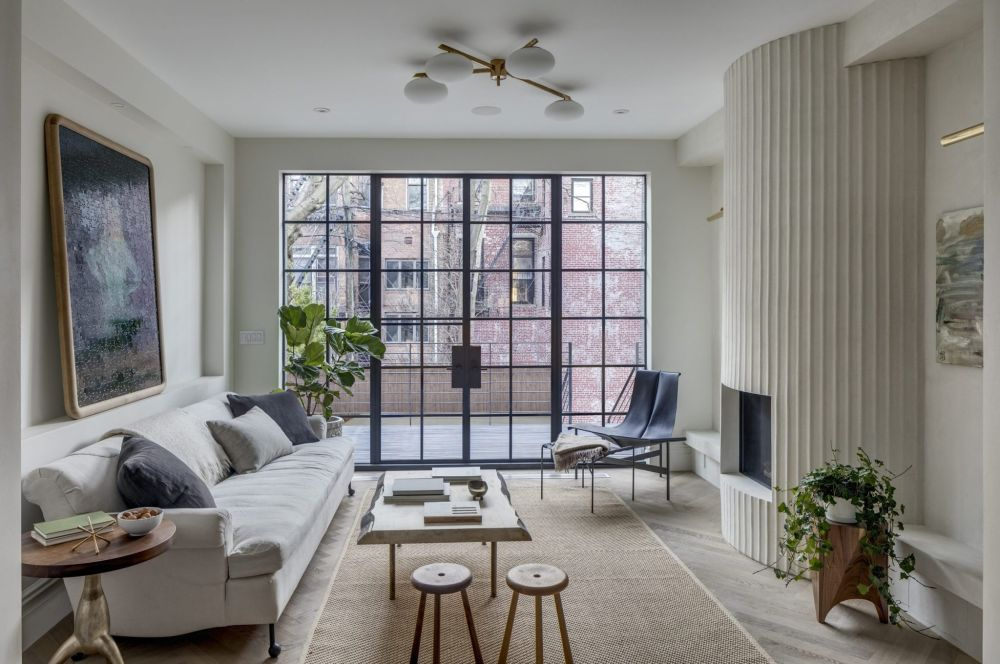 Large panel windows and doors fill the living room with natural light during the day