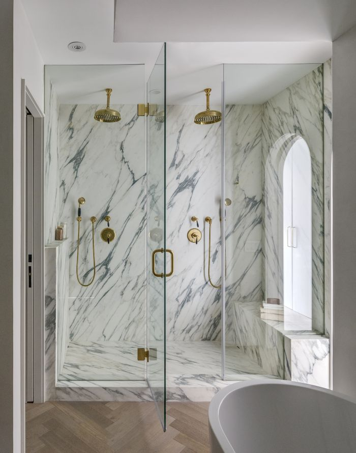 The master bathroom features a double walk-in shower with an arched window