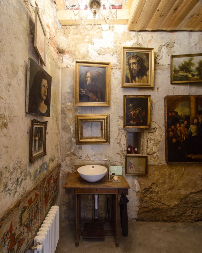The bathroom is decorated with lots of framed paintings