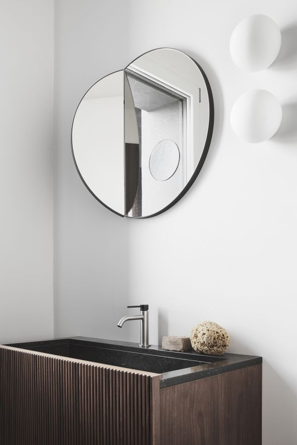 The bathroom is equally simple and elegant, featuring a chic wall mirror and a wooden vanity
