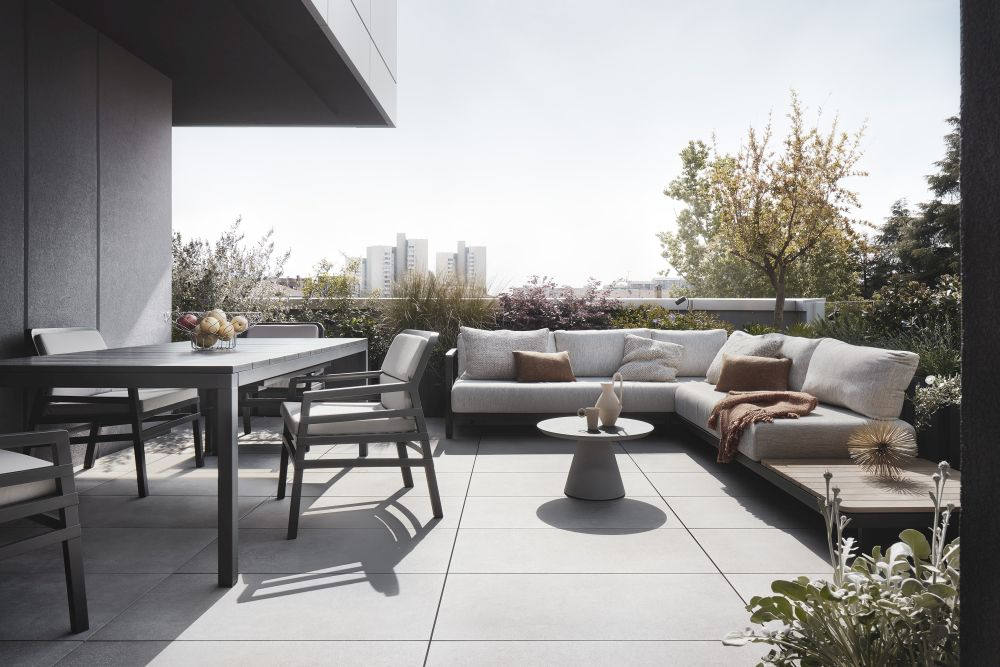 The living room opens onto a spacious terrace with a corner sectional sofa and a dining area