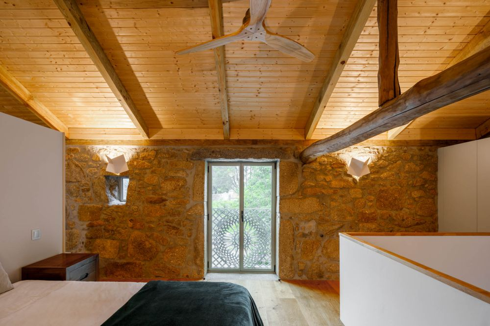 The slanted wooden ceiling combined with the stone accent wall and the lighting make this bedroom look super cozy