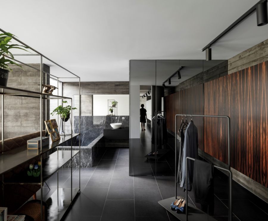 The black floor tiles inside the house are complemented by dark wood and marble surfaces