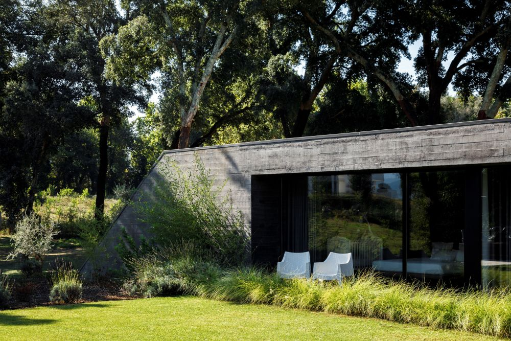 Lots of greenery, shrubbery and trees frame the house and help it blend in