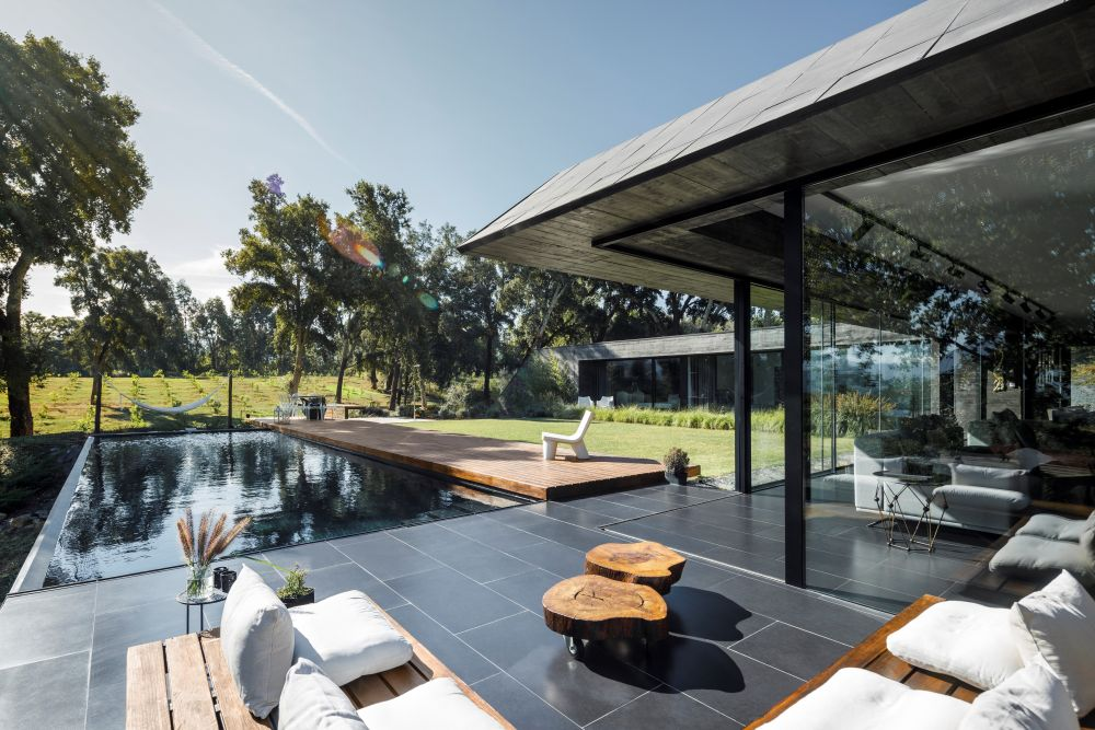 A swimming pool and a wooden deck act as bridges between the house and the open green field
