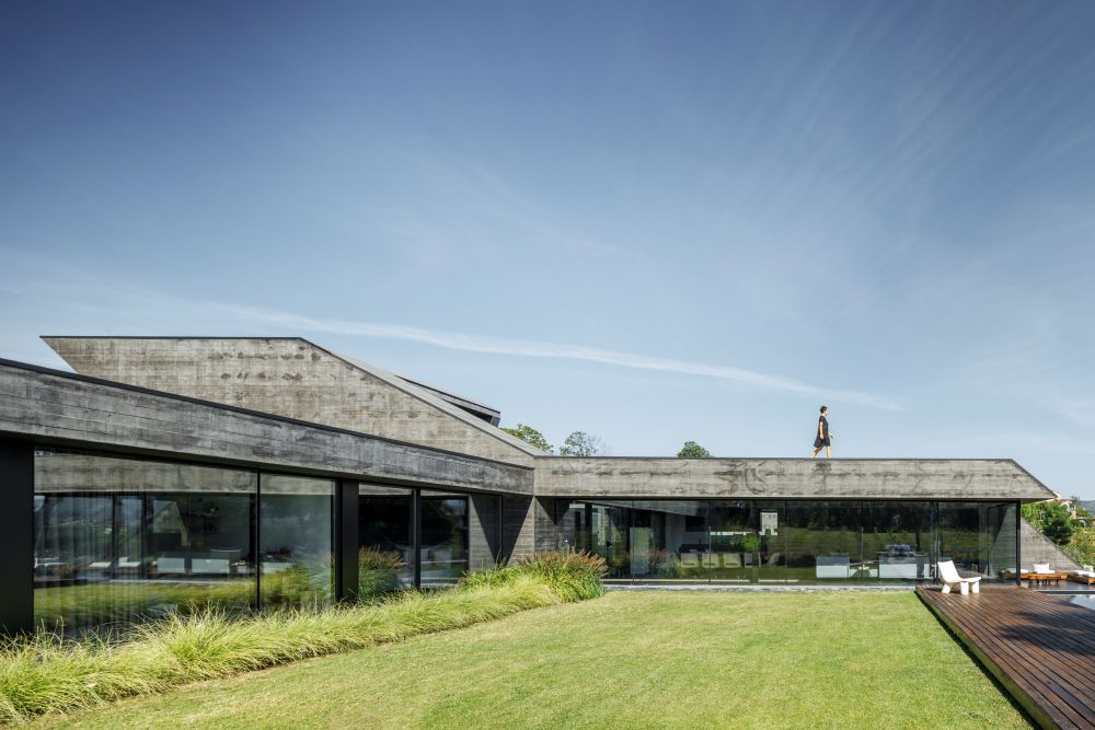 These sloped facades made out of concrete allow the building to disguise itself and to transition into the landscape more easily