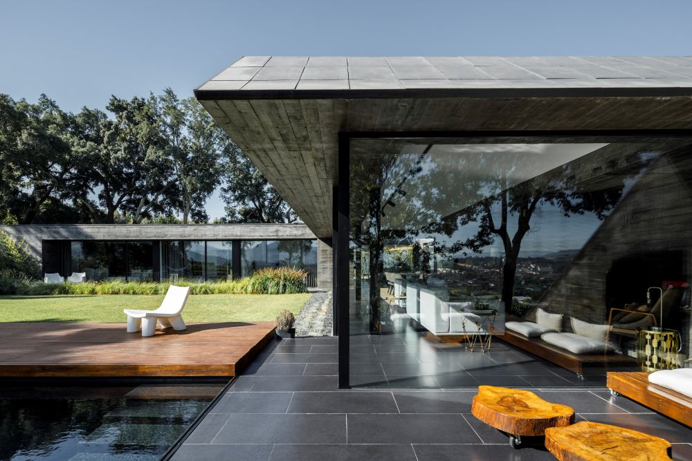 The glass walls and the continuous floor tiles allow for a seamless transition between the indoor living areas and the adjacent patio