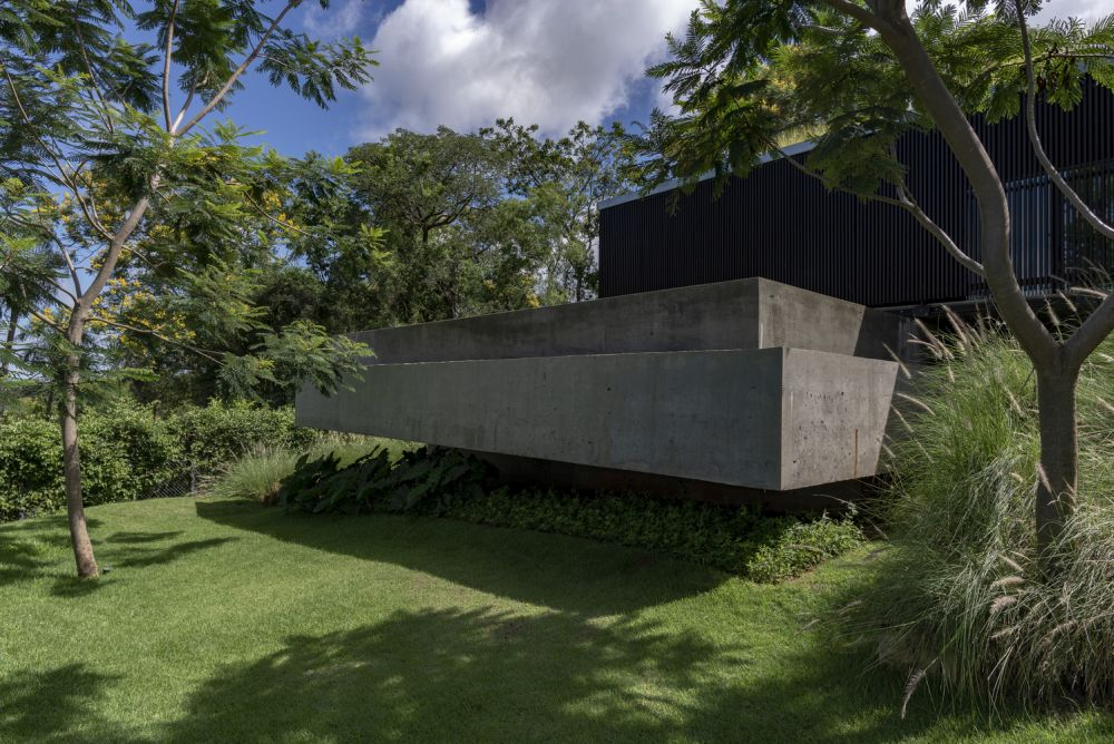 The house appears to float above the rugged topography which gives it lightweight look