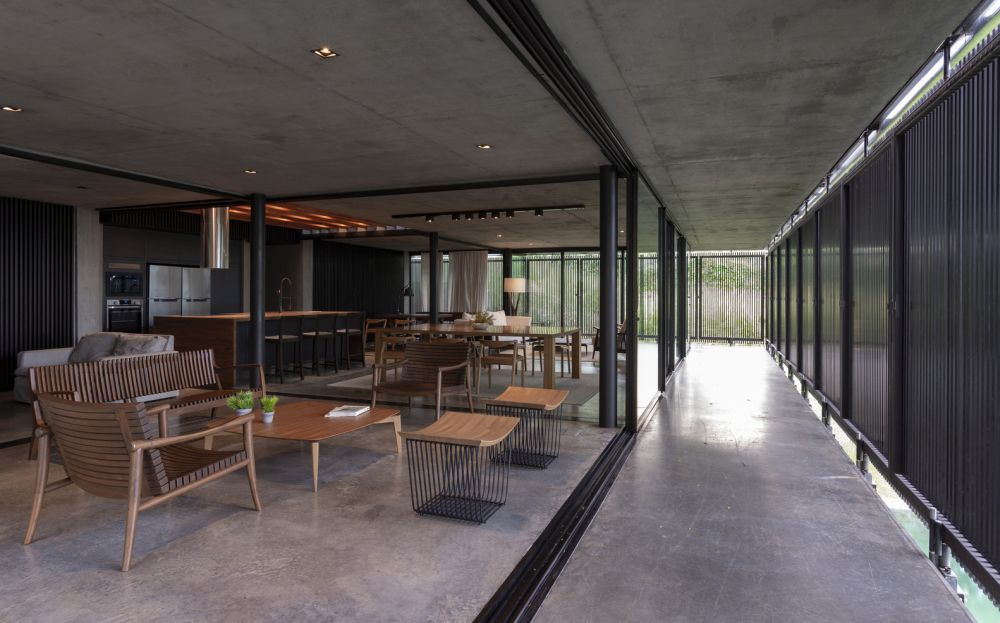 A corridor encased in glass and sliding panels separates the indoor spaces from the outdoor areas