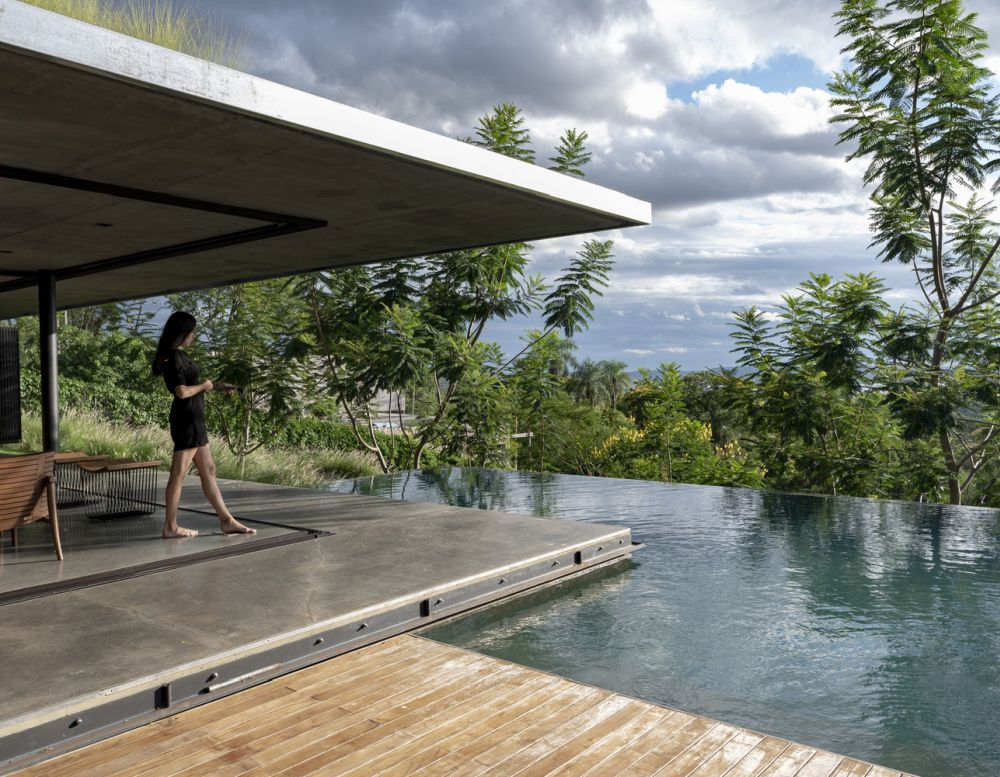 The polished concrete floor extends towards the pool area, creating a small terrace around the house