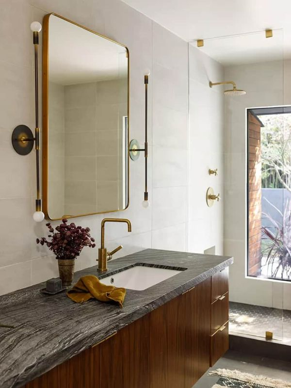 The bathroom looks very stylish thanks to the brass fixtures