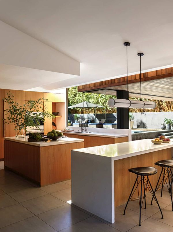 The kitchen sits at the center of the house between the social and the private areas