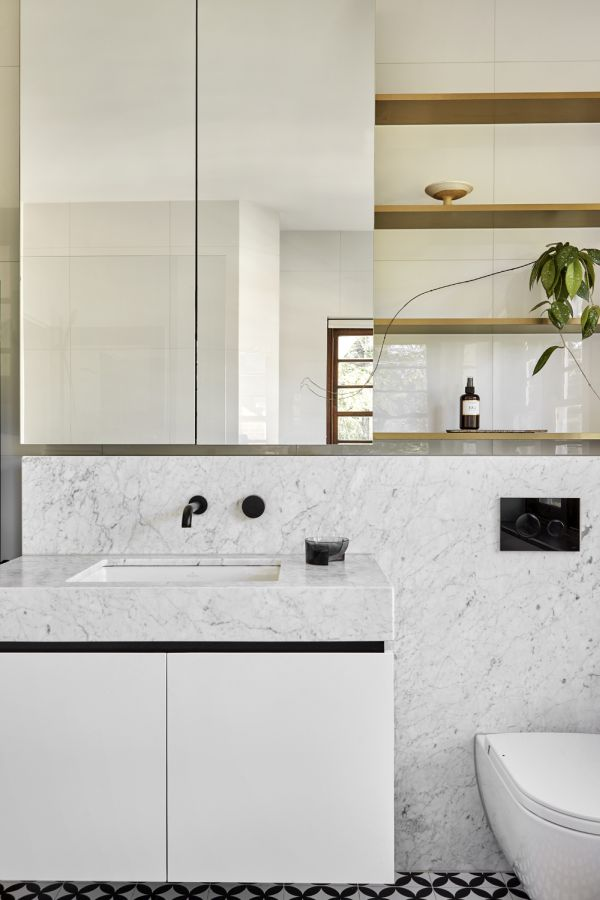The new master bathroom features white marble surfaces and big open shelves
