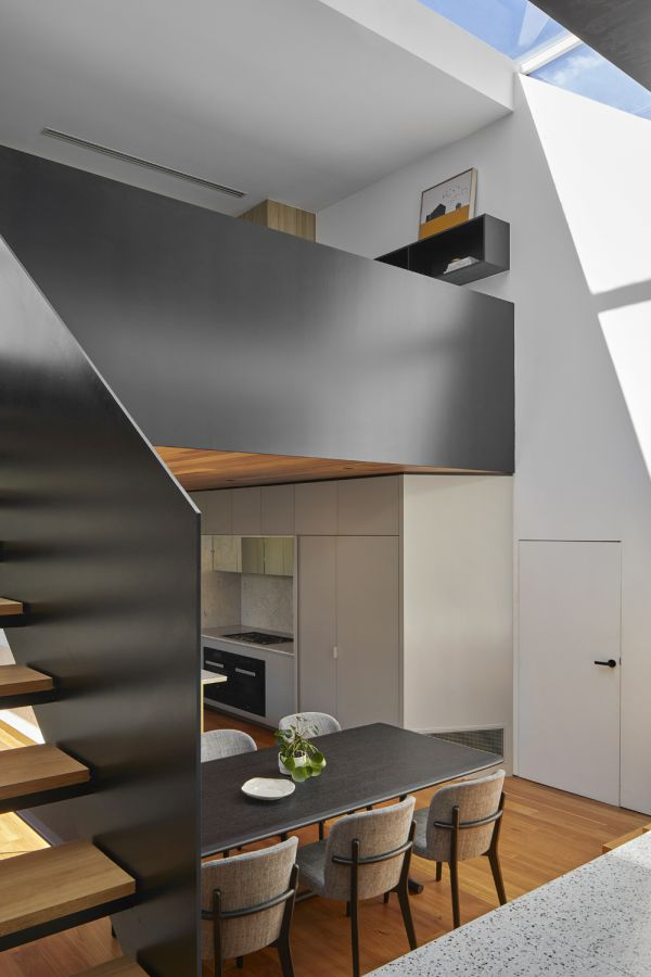 A sculptural floating staircase frames the kitchen and dining area and leads to the upper level