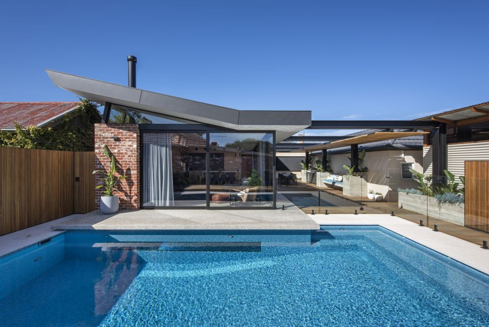The extension features an asymmetrical, sloping roof which appears to be partially floating