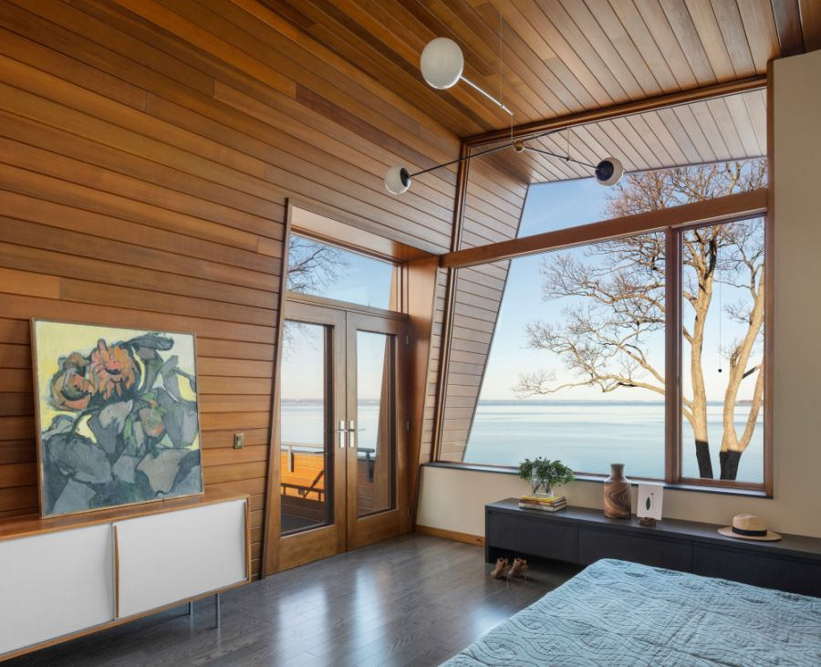 The master bedroom leads out onto a cantilevered balcony on the first floor of the house