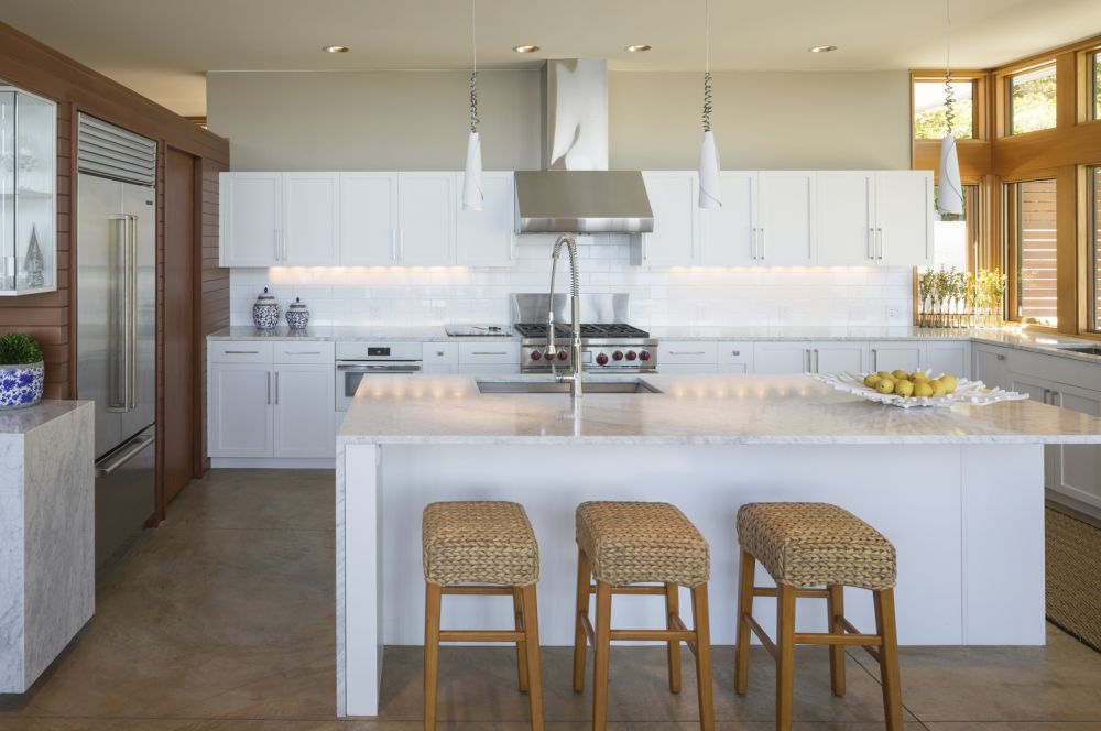 The all-white kitchen stands out against the rest of the earthy and warm colors