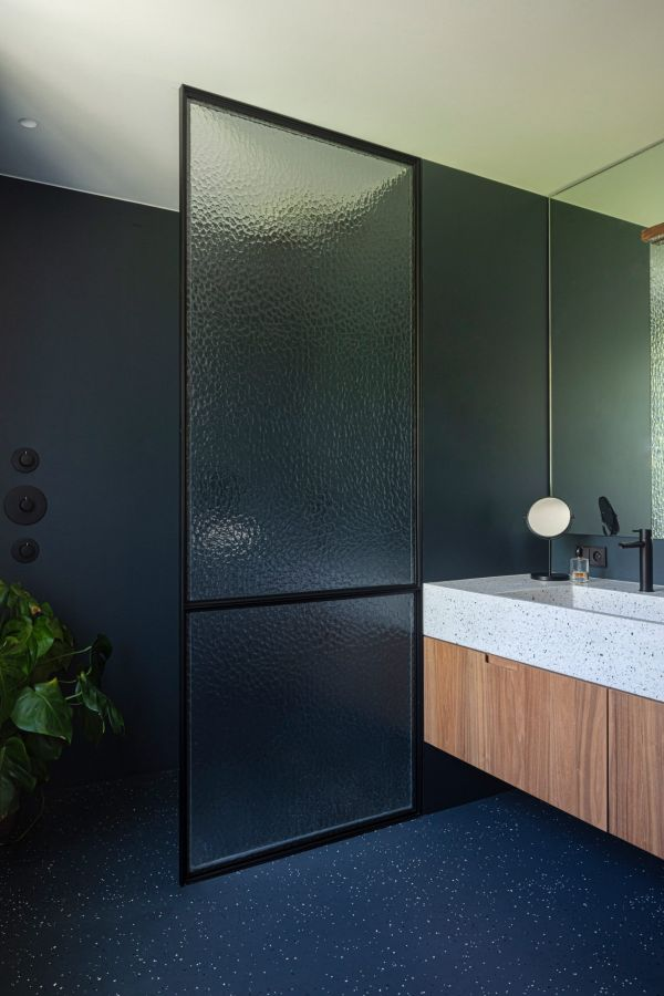 The main bathroom features a stylish color palette centered around dark blue tones