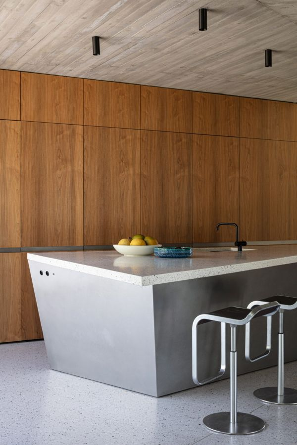 The kitchen features an angled island with a minimalistic design