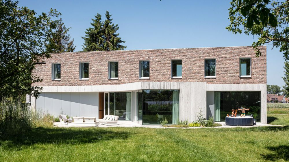 The house has a concrete ground floor and a reclaimed brick upper floor