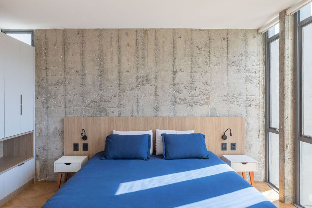 The bedroom has a similar style, featuring an exposed concrete wall and the same chevron floor pattern