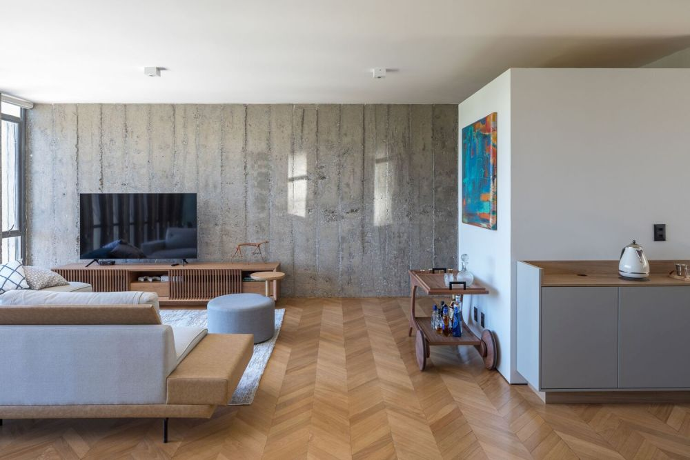 The living room uses one of the exposed concrete walls as a backdrop for its comfortable sitting area